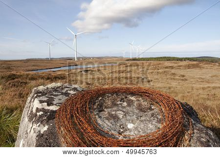 Barbed Wire On A Rock With Wind Turbines
