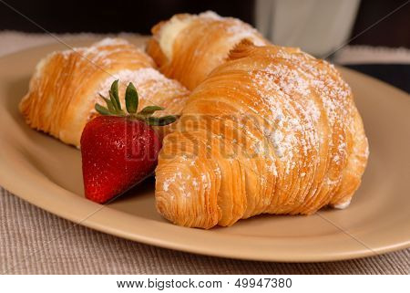 Three sfogliatelle's with strawberry on tan plate