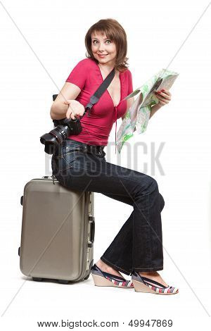 young woman tourist sitiing on the suitcase