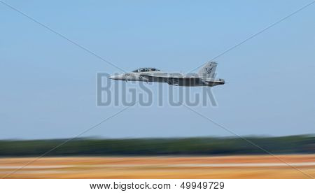 Navy jet plane flying low to the ground showing motion blur to the ground