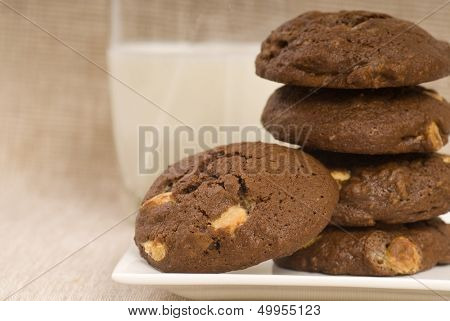 Fresh baked triple chocolate chip cookies with a glass of milk