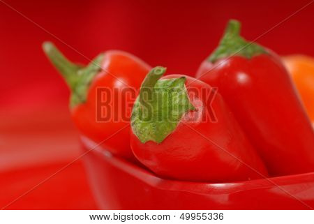Several red and orange chili peppers in a red bowl with shallow depth of field