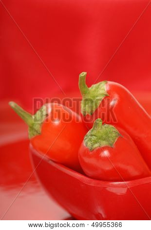 Red chili peppers in a red bowl with a red background