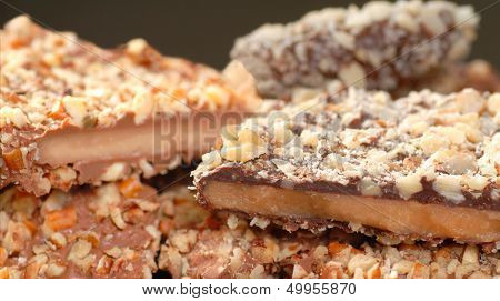 Different types of English Toffee with a variety of chocolates and nuts with a shallow depth of field.