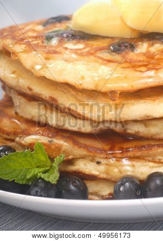 Delicious homemade blueberry pancakes with pure maple syrup dripping down them