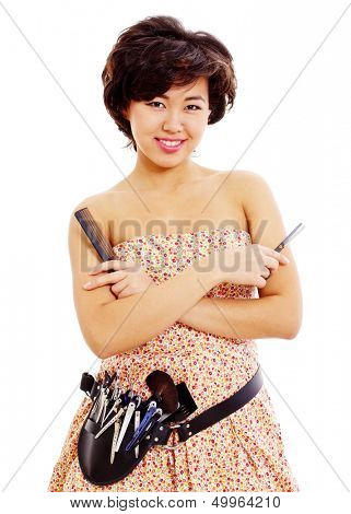 Smiling young asian master of style with scissors in right hand, comb in left and professional tools on belt. Isolated on white background, mask included