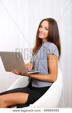 Young beautiful business woman with laptop in office