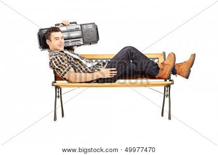 Guy holding a boombox on his shoulder and lying on a wooden bench isolated on white background