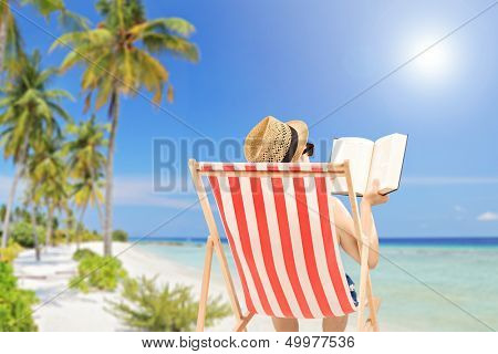 Young man lying on an outdoor chair and reading book, on a tropical beach