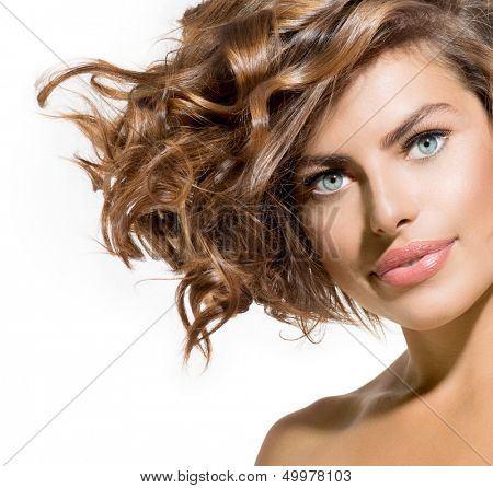 Beauty Young Woman Portrait over White Background. Beautiful Model Girl Face. Short Curly Hair, Fresh Clean Skin and Green Eyes. Hairstyle. Haircut