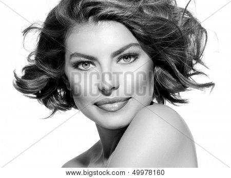 Beauty Young Woman Portrait over White Background. Beautiful Model Girl Face. Short Curly Hair, Fresh Clean Skin and Green Eyes. Hairstyle. Haircut, Beauty Make up. Black and White Portrait