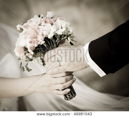 Groom handing wedding bouquet to bride