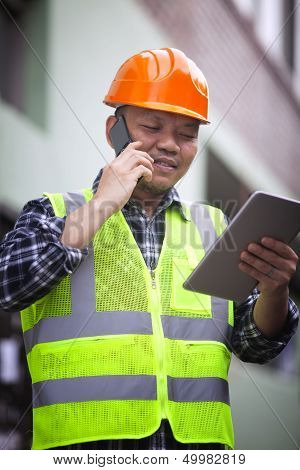 Portrait Of Construction Worker Wearing Safety Vest Talking On The Phone
