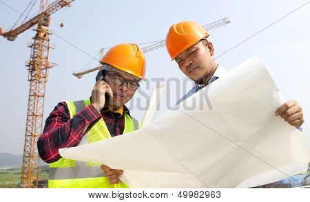 Construction Builder Looking At Plans