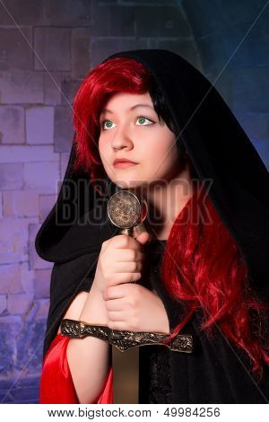 Vampire gothic woman or sorceress with green eyes and a sword