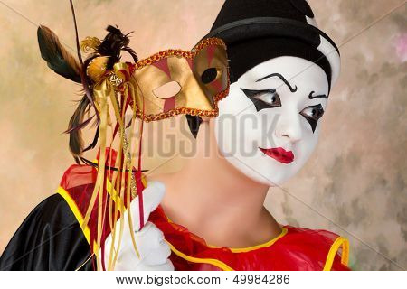 Young female pierrot holding a leather venice mask