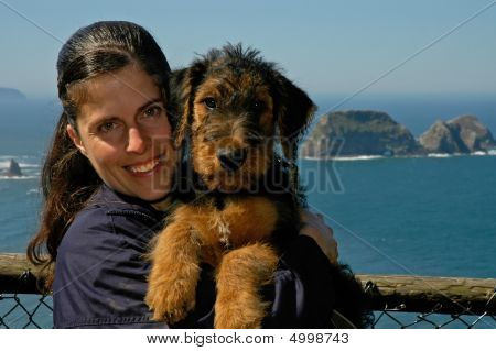 Woman Holding A Young Airedale Terrier Puppy With The Ocean In The Background