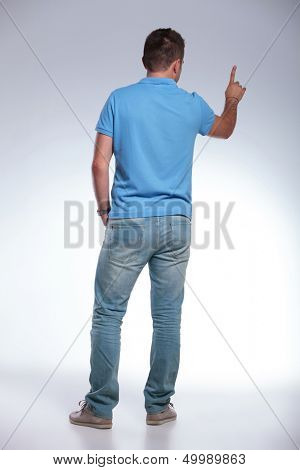 back view of a young casual man pushing an imaginary button. on gray background