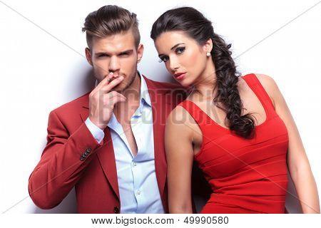 smoking hot fashion couple looking at the camera, man smoking his cigarette