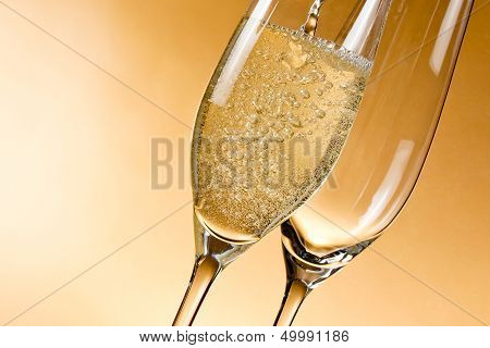 Empty Glasses Of Champagne And One Being Filled