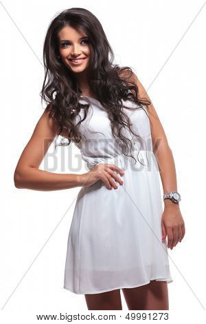 young beautiful woman standing with her hand on her hip and looking away with a smile on her face. isolated on a white background
