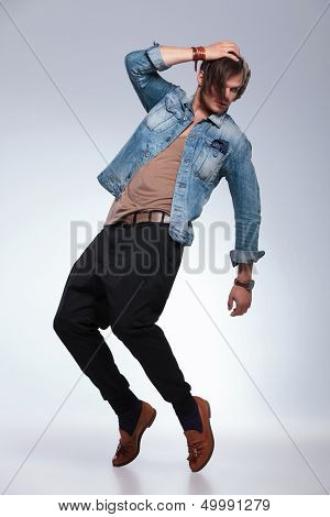 full length portrait of a casual young man balancing on his toes while holding his cap and looking to his back, away from the camera. on gray studio background