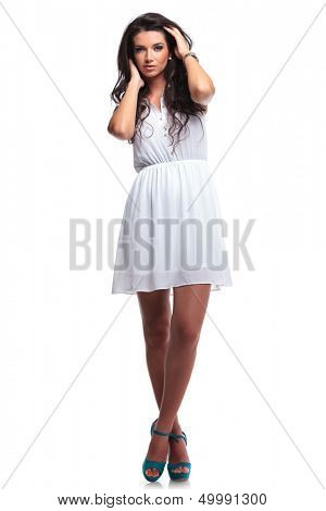 full length picture of a young beautiful woman posing with her hands through her hair and her legs crossed while looking at the camera. isolated on a white background