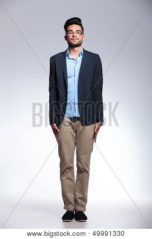 full length photo of a casual young man standing in attention with his palms along his body and looking at the camera. on gray background