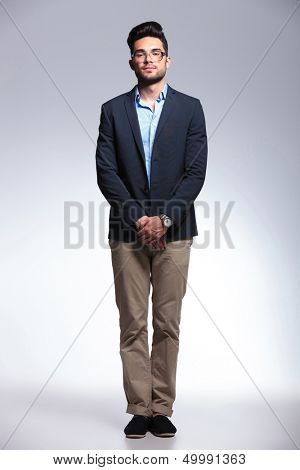 full length picture of a casual young man holding his hands together in front and looking at the camera with a serious expression. on gray background
