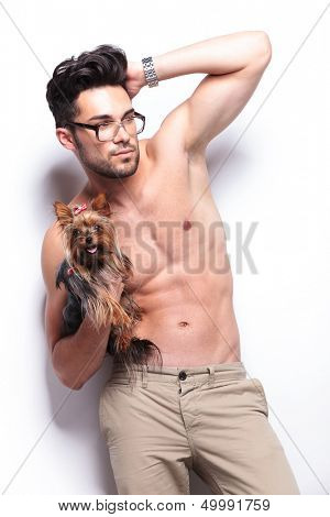 topless young man holding a puppy and passing his hand through his hair while looking away from the camera. on white background
