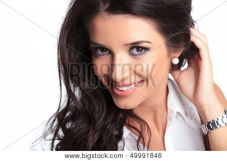 closeup picture of a young beautiful woman smiling at the camera while holding her hair behind her ear. isolated on a white background
