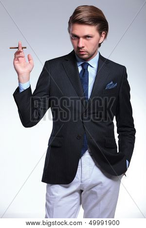young business man stylishly holding a cigarette while looking at the camera with his other hand in pocket. on a gray background