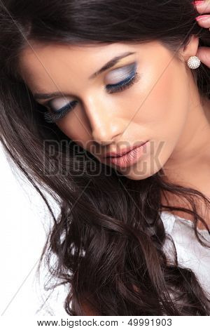 closeup photo of a young beautiful woman keeping her eyes shut and her hand behind her ear. isolated on a white background