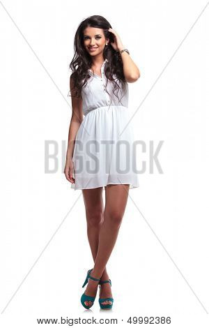 full length picture of a young beautiful woman passing her hand through her hair and smiling for the camera. isolated on a white background