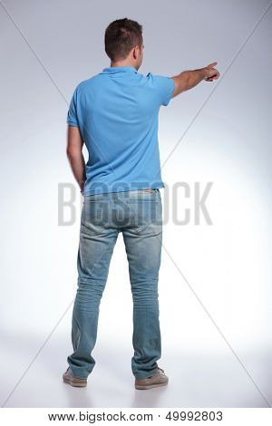 back view of a young casual man pointing away from the camera. on gray background