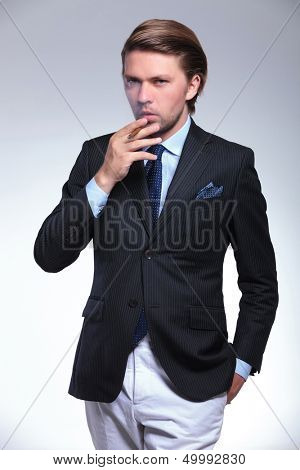 young business man with a hand in his pocket is exhaling smoke from the cigarette he is holding while looking at the camera. on a gray background