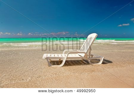 white chaise lounge at the sea