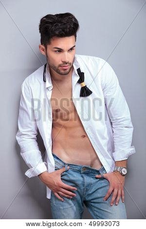 sexy casual young man with thumbs in the loops of his jeans is looking away from the camera. on gray background