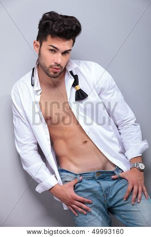 sexy casual young man holding his thumbs in the loops of his jeans and looking into the camera. on gray background