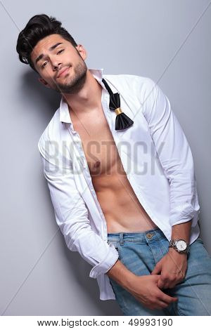sexy casual young man looking at the camera with an arrogant expression. on gray background