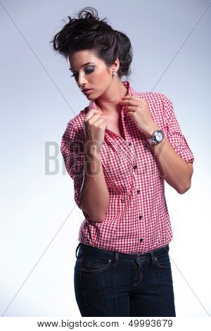 young casual woman pulling her collar and looking down to a side on a gray background