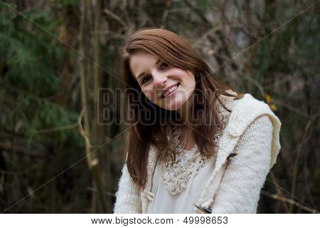 Young Woman In The Forest During Winter Smiling