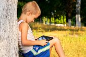 Boy Child Playing With Tablet Pc Outdoor With Forest On Background Computer Game Dependence Concept