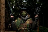 picture of paintball  - Paintball Sport Player Wearing Protective Mask Aiming Gun And Shotted Down With Paint Splash