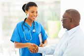 stock photo of nurse practitioner  - friendly african american medical nurse handshaking with senior patient - JPG