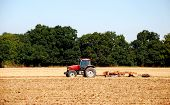 foto of cultivator-harrow  - Red tractor and disc harrow breaking up the soil after harvest in a farm field  - JPG