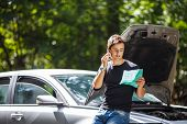 stock photo of policy  - Handsome young man calling for assistance with his car broken down by the roadside - JPG
