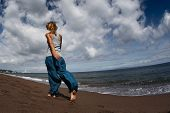 picture of wet pants  - Young lady walking on a wet sandy beach - JPG