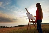 stock photo of arts crafts  - artist girl painting an sunset sea landscape - JPG