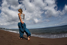 foto of wet pants  - Young lady walking on a wet sandy beach - JPG